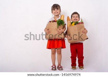 Kids holding paper grocery bag full of vegetables milk, bread. Happy family with grocery bag full of healthy food isolated on white. Food in paper bag. Grocery shopping concept.