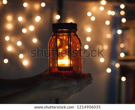 kids holds Christmas lantern in hands on lights bokeh background. New year celebration concept, festive mood