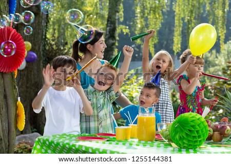 Kids in birthday hats and playing with balloon during garden party #1255144381