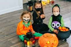 Kids in carnival costumes are celebrating Halloween, wearing face masks and playing with pumpkins and candies indoors
