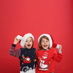 Kids in Christmas sweaters and Santa hats on red background