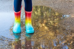 Kids in fall. close-up of a baby girls legs with rainbow rubber boots jumping into a puddle on an autumn walk. Children have fun playing outdoors. Waterproof boots for little girl