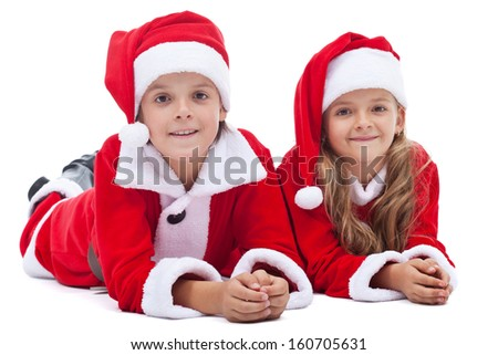 Kids in santa costumes at christmas time laying on the floor - isolated