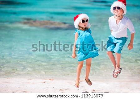 Kids in Santa hats having fun at tropical beach