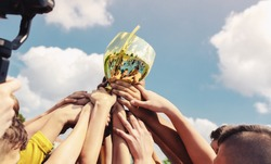 Kids in sports team lift up the golden cup trophy after winning the final tournament match. Children celebrate success in sports. Winning championship in sports