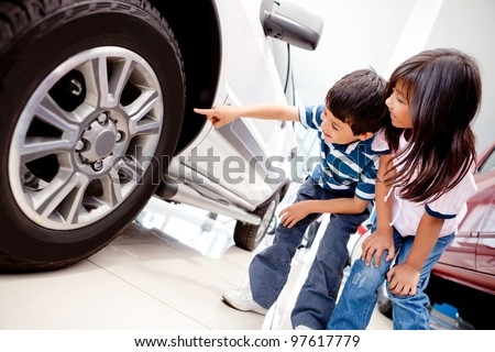 Kids in the dealer looking at car wheels