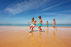 Kids in the middle of soccer game play on a beach