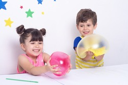 Kids inflates a big bubble from a pink and yellow slime. Children squeeze and stretching toy goo slime.