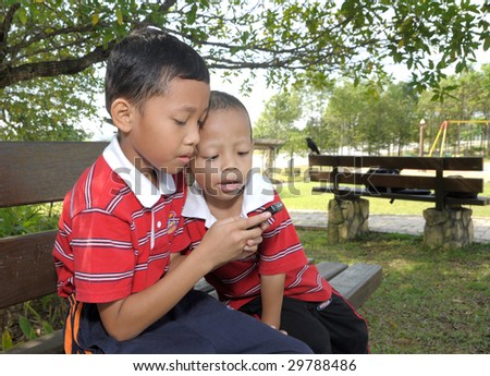 Kids is playing games on hand phone - stock photo