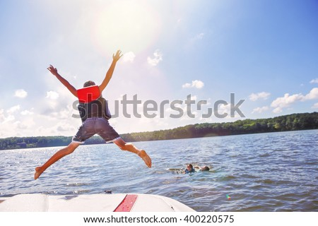 kids jumping off a boat into...