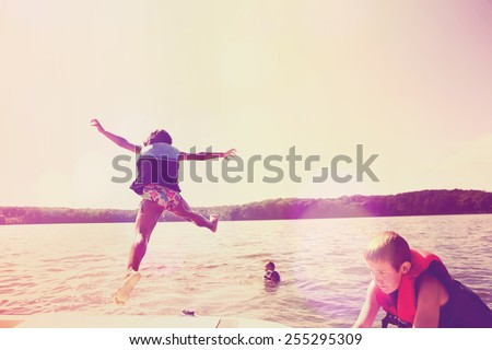 Kids jumping off a boat into the lake. Instagram effect.