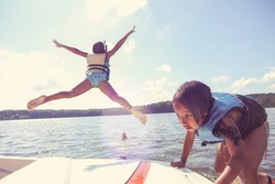 Kids jumping off a boat into the lake. Instagram effect.  Focus on boat and girl