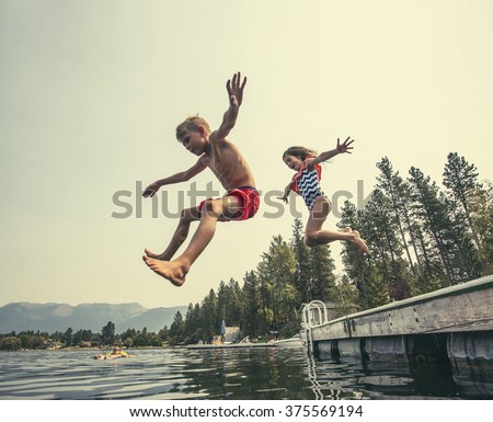 kids jumping off the dock into...