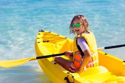 Kids kayaking in ocean. Children in kayak in tropical sea. Active vacation with young kid. Little girl in canoe on beautiful beach. Holiday activity with preschool child. Family water fun.