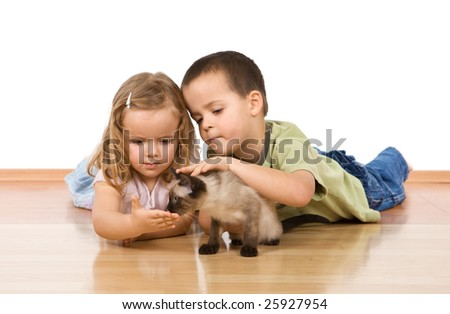 Kids laying on the floor caressing their kitten