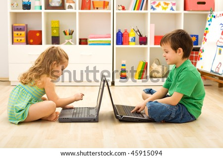 Kids learning and playing computer games sitting on the floor with laptops