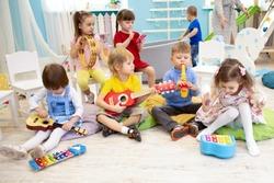 Kids learning musical instruments on lesson in kindergarten or preschool