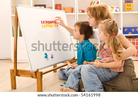 Kids learning the numbers with their mother and  a magnetic board