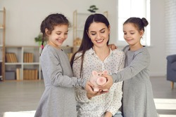Kids learning the value of money. Happy smiling young mother and two cute little daughters holding piggy bank together. Concept of family finance, budget management, saving up for children's education