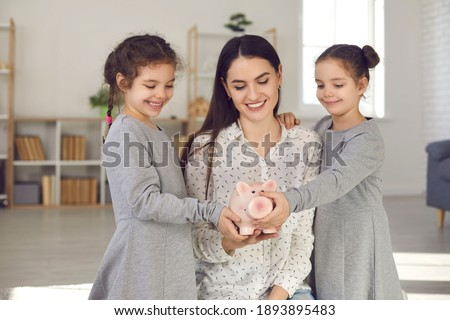Kids learning the value of money. Happy smiling young mother and two cute little daughters holding piggy bank together. Concept of family finance, budget management, saving up for children's education Stock fotó ©