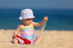Kids lifestyle outdoor. Happy cute girl in bikini and panama playing with sand on the beach of sea. Summer vacation and family travel concept. Little baby girl sitting on the sand near the sea