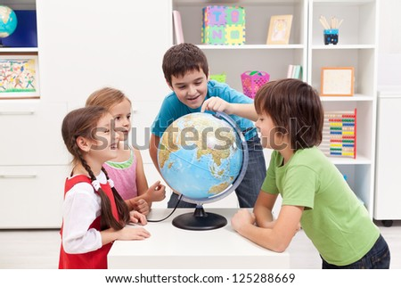 Kids looking at earth globe and telling stories