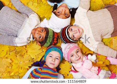 Kids lying on yellow fall foliage