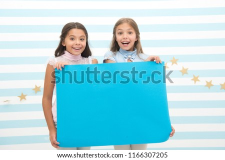 kids make advertisement. advertising your product. smiling little girls kids hold blue advertisement poster for copy space. little girls with blue paper #1166307205
