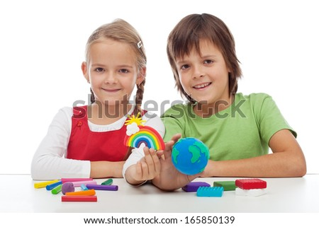 Kids making colorful ecology theme clay figures - holding earth globe and rainbow
