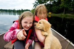 kids on a boat with a puppy
