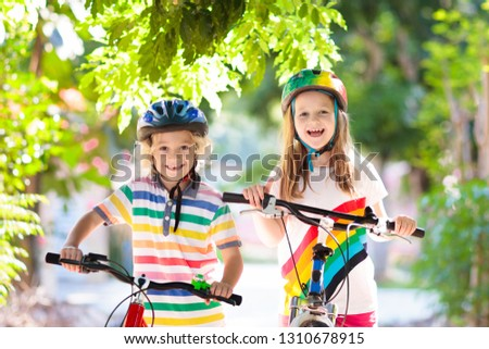 Kids on bike in park. Children going to school wearing safe bicycle helmets. Little boy and girl biking on sunny summer day. Active healthy outdoor sport for young child. Fun activity for kid. #1310678915