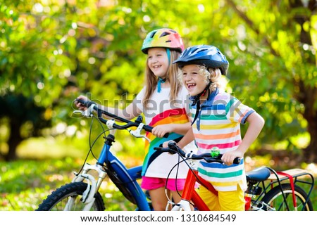 Kids on bike in park. Children going to school wearing safe bicycle helmets. Little boy and girl biking on sunny summer day. Active healthy outdoor sport for young child. Fun activity for kid. #1310684549