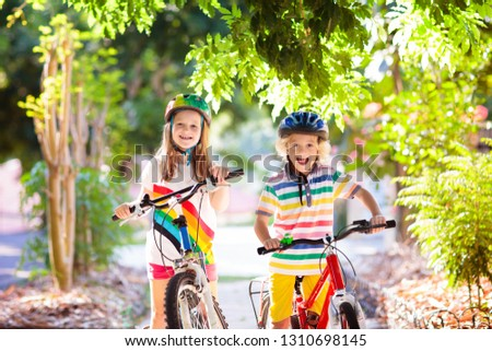 Kids on bike in park. Children going to school wearing safe bicycle helmets. Little boy and girl biking on sunny summer day. Active healthy outdoor sport for young child. Fun activity for kid. #1310698145