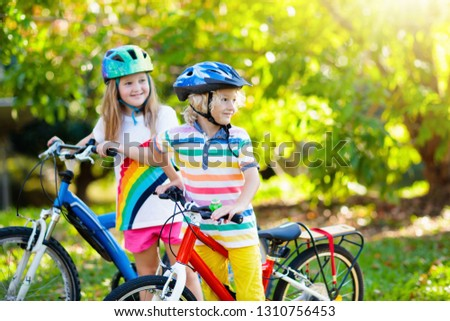 Kids on bike in park. Children going to school wearing safe bicycle helmets. Little boy and girl biking on sunny summer day. Active healthy outdoor sport for young child. Fun activity for kid. #1310756453