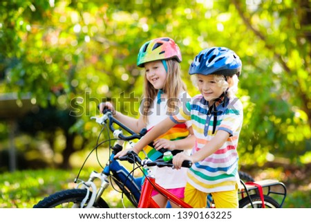 Kids on bike in park. Children going to school wearing safe bicycle helmets. Little boy and girl biking on sunny summer day. Active healthy outdoor sport for young child. Fun activity for kid. #1390163225