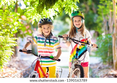 Kids on bike in park. Children going to school wearing safe bicycle helmets. Little boy and girl biking on sunny summer day. Active healthy outdoor sport for young child. Fun activity for kid.