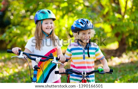 Kids on bike in park. Children going to school wearing safe bicycle helmets. Little boy and girl biking on sunny summer day. Active healthy outdoor sport for young child. Fun activity for kid. #1390166501