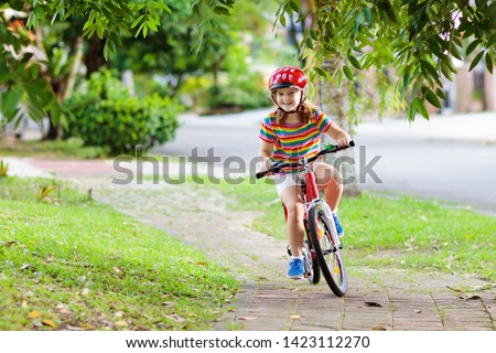 Kids on bike in park. Children going to school wearing safe bicycle helmets. Little girl biking on sunny summer day. Active healthy outdoor sport for young child. Fun activity for kid
