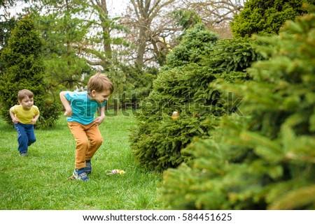 Kids on Easter egg hunt in blooming spring garden.