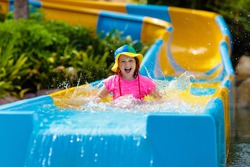 Kids on water slide in aqua park. Children having fun on water slides on family summer vacation in tropical resort. Amusement park with wet playground for young child and baby.