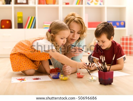 Kids painting hands and making prints with their mother sitting on the floor