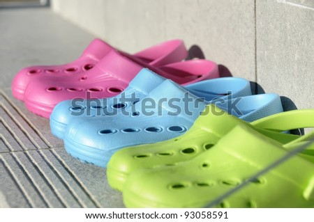 Kids plastic summer clogs in a row on a step. Shot through glass. Shallow depth of field. Focus on the Blue clog.