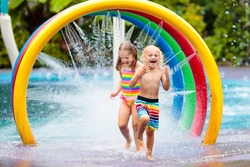 Kids play in aqua park. Children at water playground of tropical amusement park. Little girl and boy at swimming pool. Child playing at water slide on summer vacation in Asia. Swim wear for young kid.