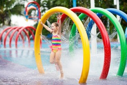 Kids play in aqua park. Children at water playground of tropical amusement park. Little girl at swimming pool. Child playing at water slide on summer vacation in Asia. Swim wear for young kid.