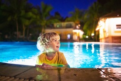 Kids play in outdoor swimming pool of tropical resort at night. Evening swim on exotic island. Baby learning to dive. Children playing in water. Beach and summer fun.