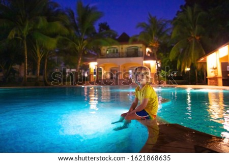 Kids play in outdoor swimming pool of tropical resort at night. Evening swim on exotic island. Baby learning to dive. Children playing in water. Beach and summer fun. Stock foto ©