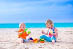 Kids play on a beach. Children building sand castle on tropical island. Summer water fun for family. Boy and girl with toy buckets and spade at the sea shore. Ocean vacation with baby and toddler kid.