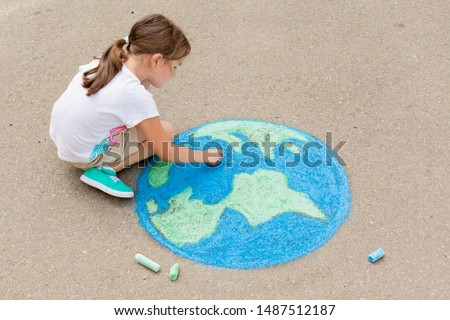 Kids play outdoors. Child girl draws a planet globe with a map of the world colored chalk on the pavement, asphalt. Earth, peace day concert.