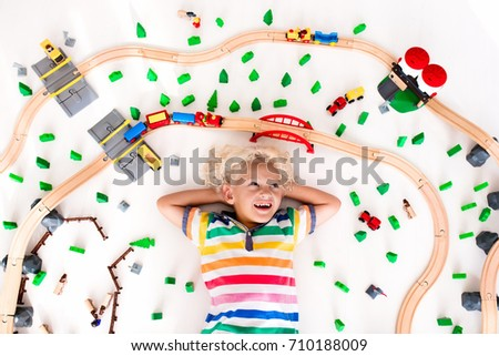 Kids play with toy train railway. Child playing with wooden trains. Toys for little boy. Preschooler building rail road and blocks at home or daycare, preschool. Kindergarten educational games. #710188009