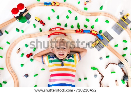 Kids play with toy train railway. Child playing with wooden trains. Toys for little boy. Preschooler building rail road and blocks at home or daycare, preschool. Kindergarten educational games. #710210452